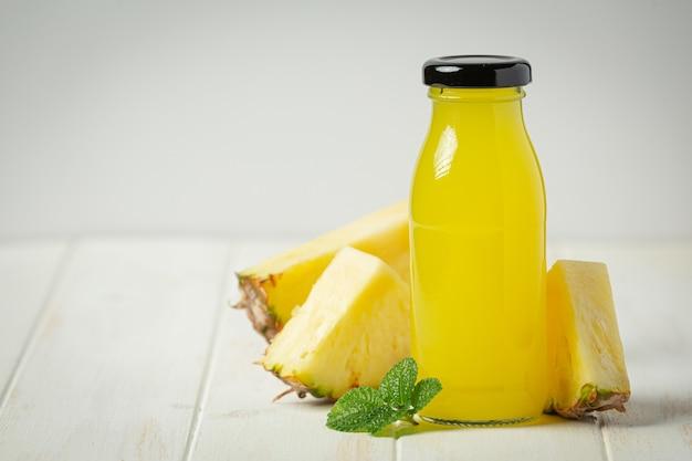 Jus d'ananas sur une surface en bois blanche