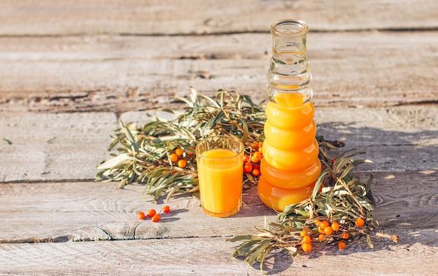 Le jus d'argousier dans une carafe et un verre est sur un fond en bois ancien. relaxation et phytothérapie, boisson anti-froid, saison grippale