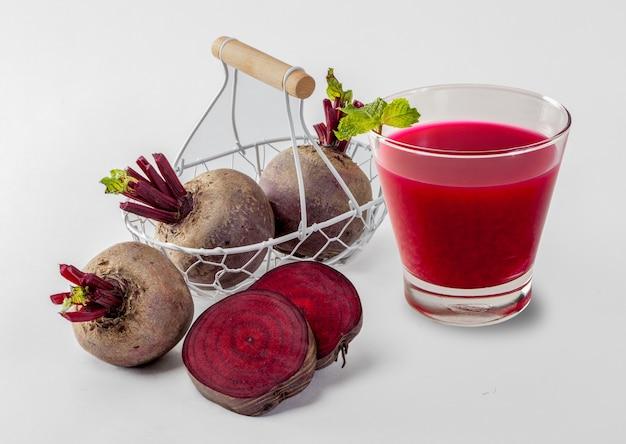 Jus de betterave pressé à froid dans du verre, légume cru sain et boisson aux fruits pour la désintoxication.
