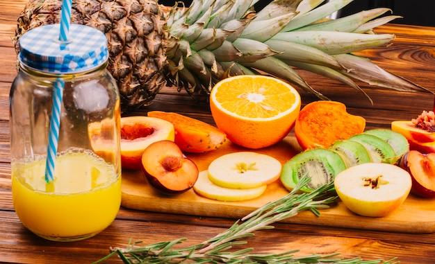 Jus bocal avec des tranches de fruits sur une planche à découper et du romarin