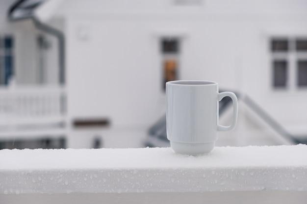 Jus de canneberge en verre céramique blanc sur terrasse en hiver