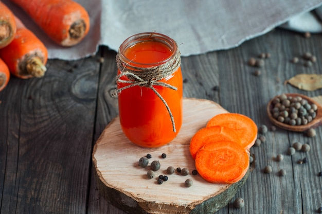 Jus de carotte avec un bocal en verre sur une surface en bois