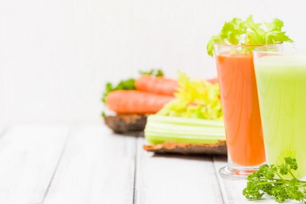 Jus de carotte et de céleri avec des légumes frais sur des plaques d'écorce sur fond en bois - boisson végétarienne