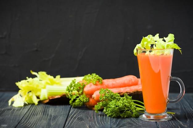 Jus de carotte et de céleri avec des légumes frais sur des plaques d'écorce sur un fond en bois noir