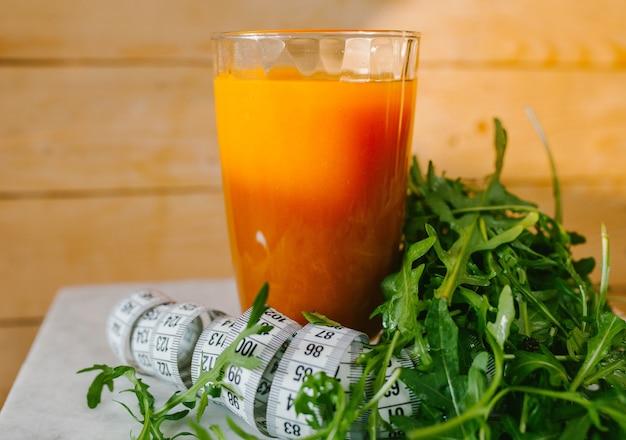 Jus de carotte dans un verre avec du ruban adhésif et de la laitue