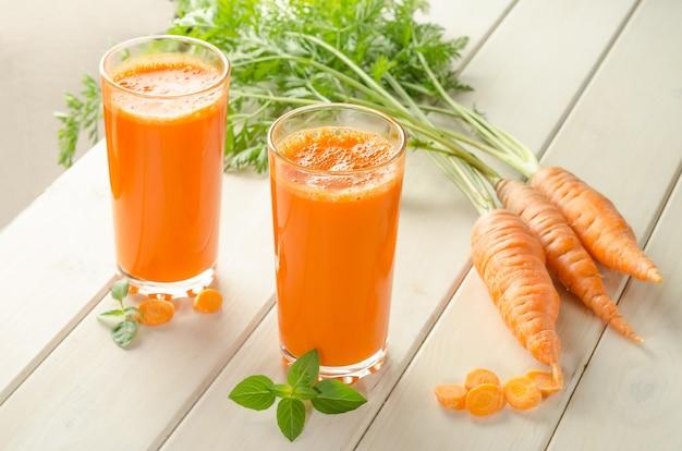 Jus de carotte fraîchement pressé dans un verre sur une table en bois blanc avec des carottes fraîches