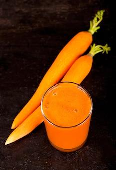 Jus de carotte frais pressé sur fond de bois
