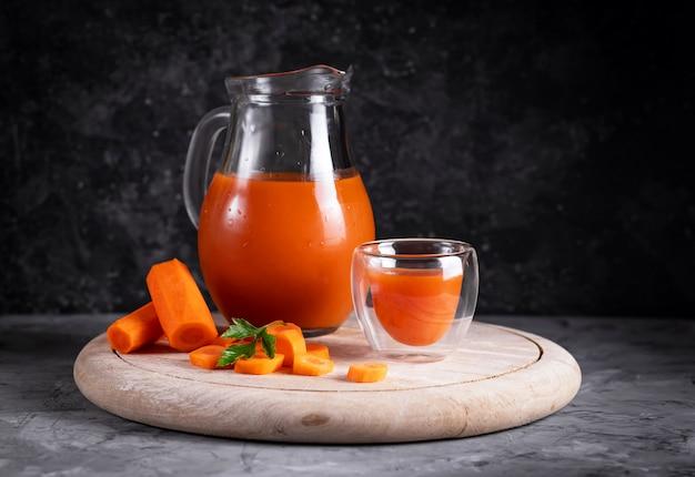 Jus de carotte et d'orange dans une cruche sur une planche ronde en bois en discret