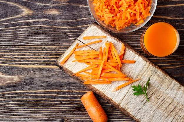 Jus de carottes et carottes tranchées sur table en bois