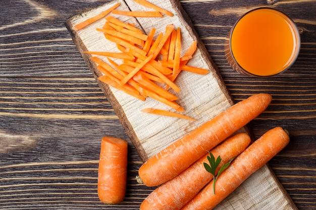 Jus de carottes et carottes en tranches sur fond de bois