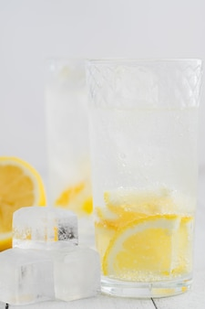 Jus de citron, eau de désintoxication. eau minérale infusée de citrons. table en bois blanc.