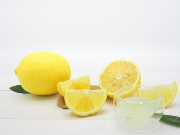 Jus de citron frais dans un petit bol et une tranche de citron sur fond de bois blanc