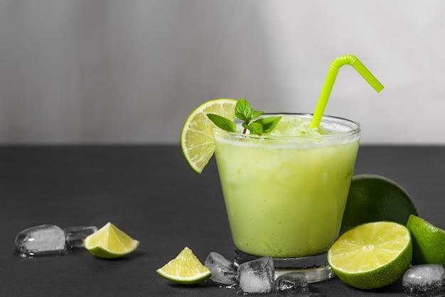 Jus de cocktail avec citron vert, menthe et glace. accessoires de boisson de bar sur fond de tableau noir.
