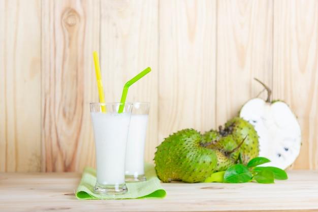 Jus de corossol avec fruits corossol sur table en bois.