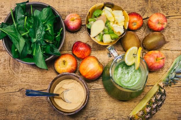 Jus d'épinards pressé à froid dans un pot entouré des ingrédients utilisés