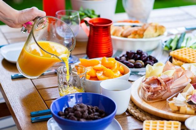 Le jus est versé dans un verre jus d'orange pour le petit déjeuner table avec de la nourriture pour le petit déjeunerorange