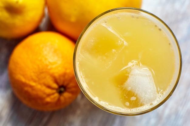 Jus frais dans un verre avec de la glace sur la table et des oranges