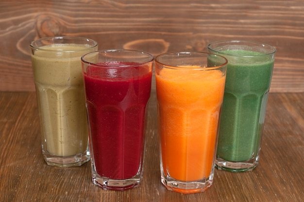 Jus frais naturels de citrouille, betteraves, pommes et un verre de spiruline sur une table en bois