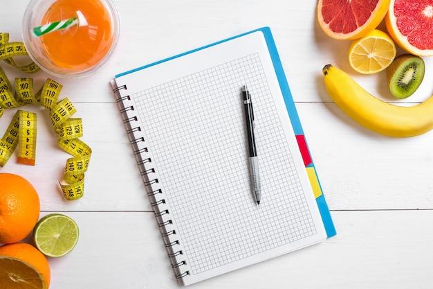 Jus frais en verre d'agrumes citron pamplemousse orange cahier avec crayon sur bois blanc...