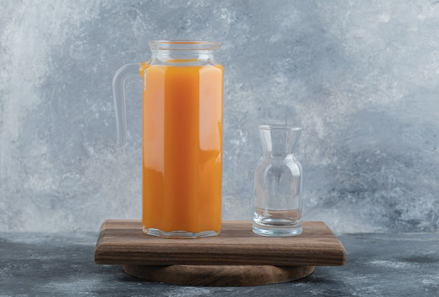Jus frais et verre vide sur planche de bois.