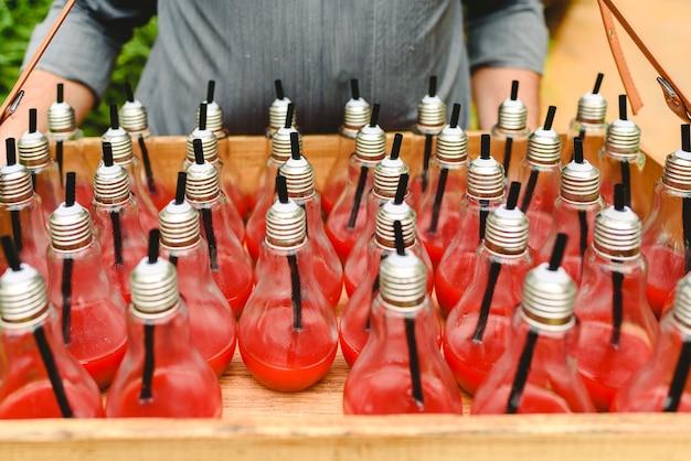 Le jus de fraise est servi de façon amusante dans des ampoules de cristal.