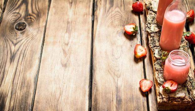 Jus de fraise sur un plateau de bouleau. sur table en bois.