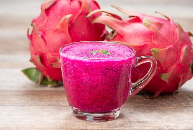 Jus de fruit frais de dragon rouge (pitaya) dans une tasse en verre.