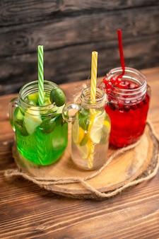 Jus de fruits biologiques naturels en bouteilles servis avec des tubes sur une planche à découper en bois