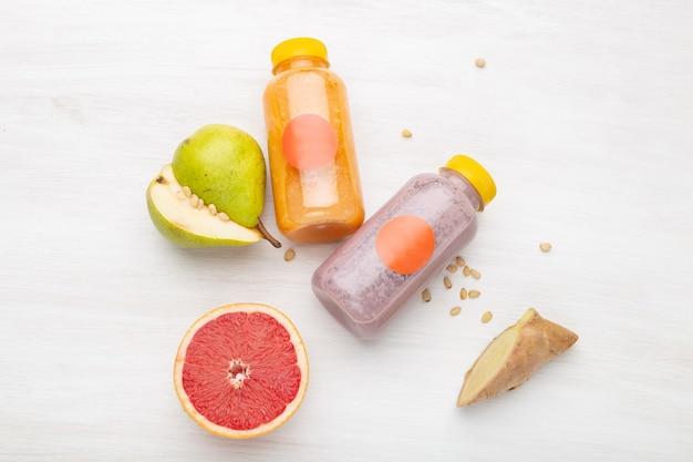 Jus de fruits dans un bocal à côté de tranches de poire et de pignons de pin debout sur un tableau blanc. concept de collation saine et déjeuner au travail.