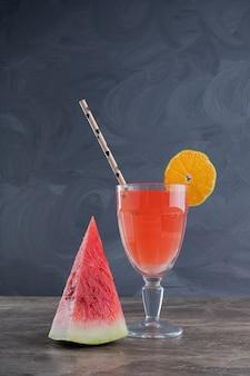 Jus de fruits frais au citron et paille sur marbre