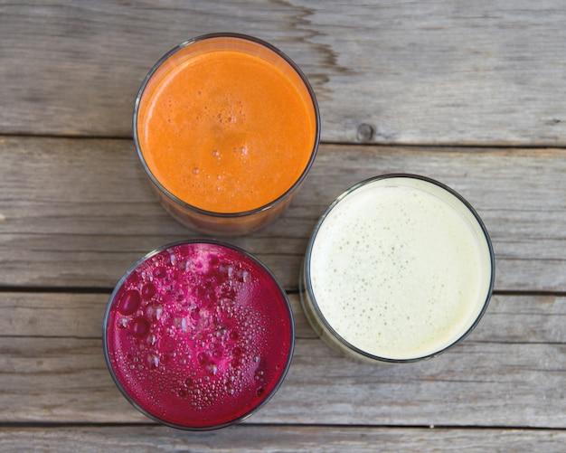 Jus de fruits frais. betterave rouge, chou et carotte sur une vue de dessus de table en bois