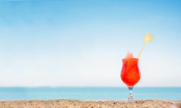 Jus de fruits sur la plage. pastèque fraîche sur le sable dans le contexte d'un paysage marin