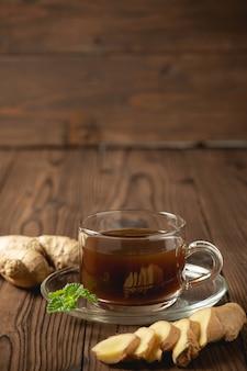 Jus de gingembre chaud et gingembre tranchés sur une table en bois.