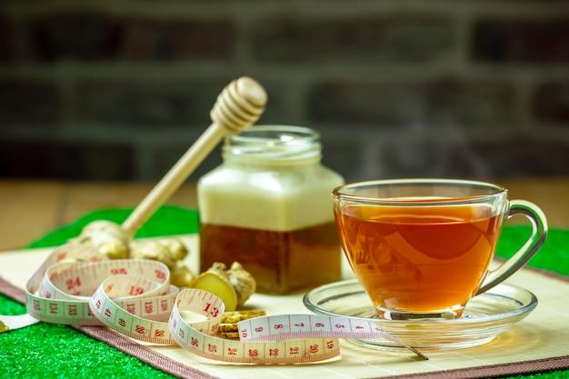Jus de gingembre dans une tasse transparente et un pot de miel placé à côté avec un ruban à mesurer.concept de la santé.