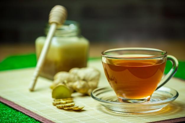 Le jus de gingembre dans une tasse transparente et un pot de miel placé à côté d'un ruban à mesurer.