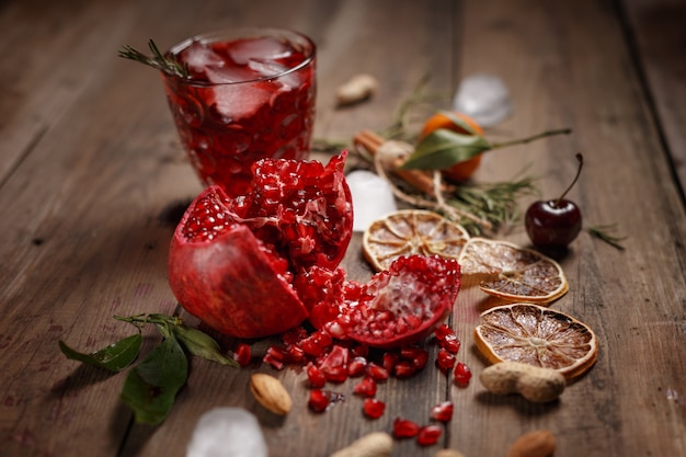Jus de grenade avec des grenades et des fruits secs sur une table en bois. style campagnard.