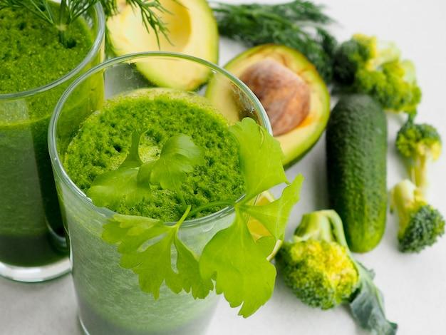 Jus de légumes verts en bonne santé sur une table en bois