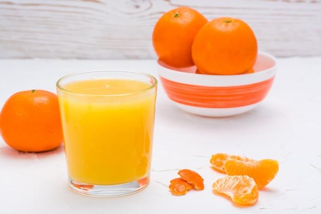Jus de mandarine dans un verre et mandarines mûres sur une table