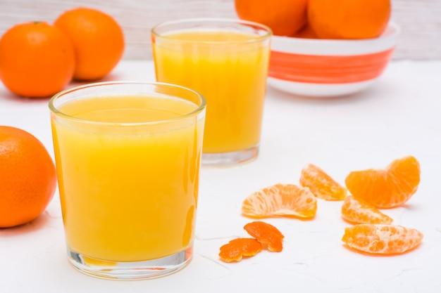 Jus de mandarine dans un verre et tranches de mandarines sur une table