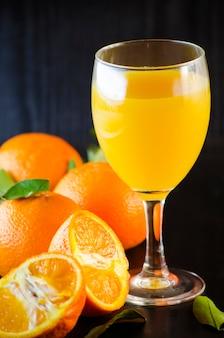 Jus de mandarine frais bio naturel dans un verre sur fond sombre
