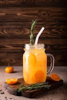 Jus de mandarine avec quartiers de mandarine et glace dans une tasse en verre