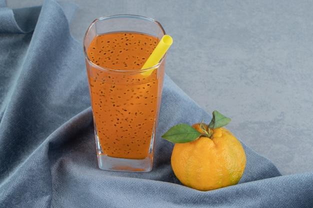 Jus et mandarine traités, sur la serviette, sur le fond bleu. photo de haute qualité