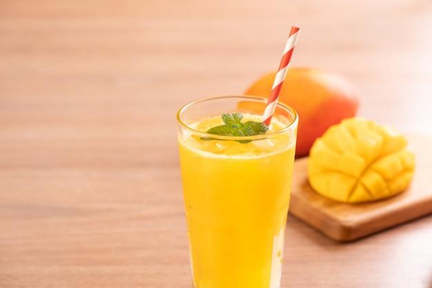 Jus de mangue fraîche avec une belle chair de pulpe hachée sur fond de table en bois clair