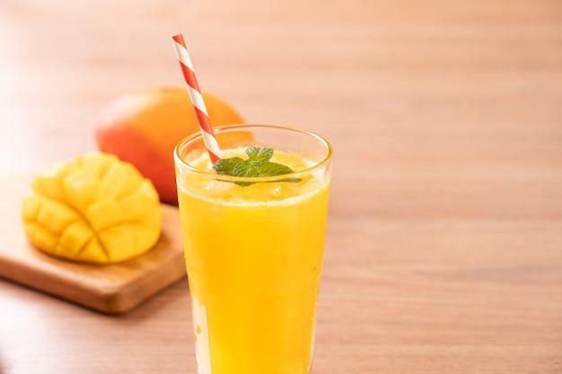 Jus de mangue fraîche avec une belle chair de pulpe hachée et de la paille sur fond de table en bois clair