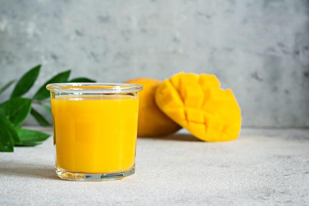 Jus de mangue fraîche dans un verre en verre avec tranche de mangue sur fond gris
