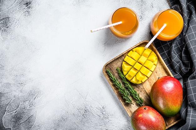 Jus de mangue smoothie aux fruits tropicaux frais et mangue fraîche. vue de dessus. espace copie