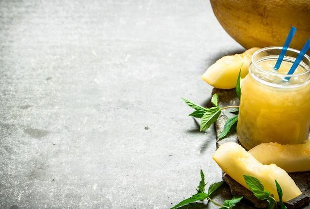 Jus de melons à la menthe et à la pulpe. sur un fond de pierre.