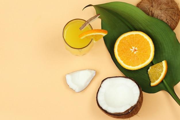 Jus de noix de coco, noix et orange, feuille de palmier sur fond beige