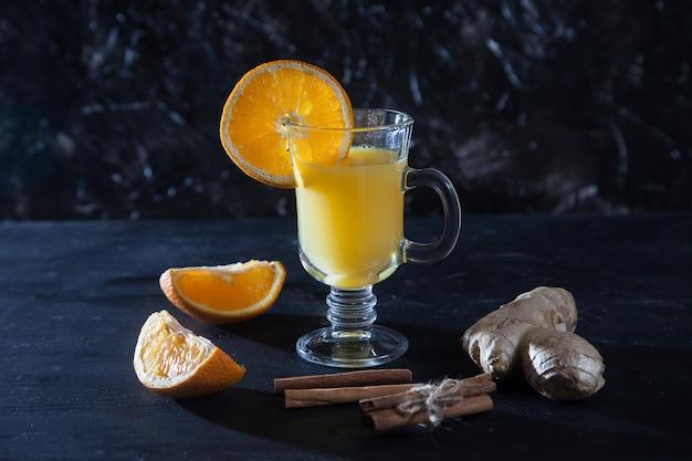 Jus d'orange au gingembre dans une tasse en verre, gingembre, cannelle sur fond noir. fraîcheur. détox.