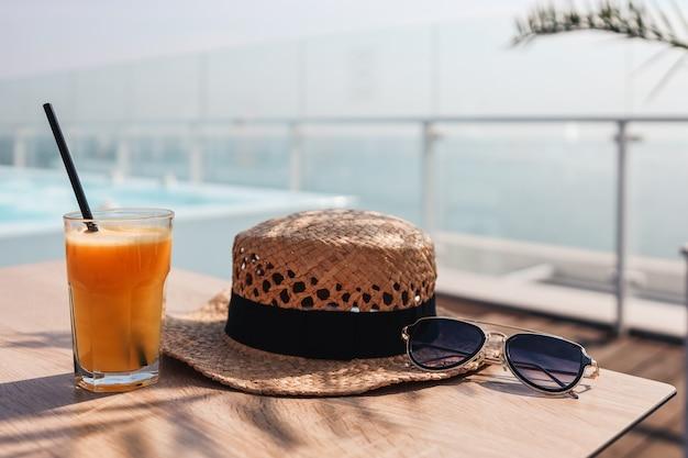 Jus d'orange, chapeau de paille et verres dans un café sur fond de mer.